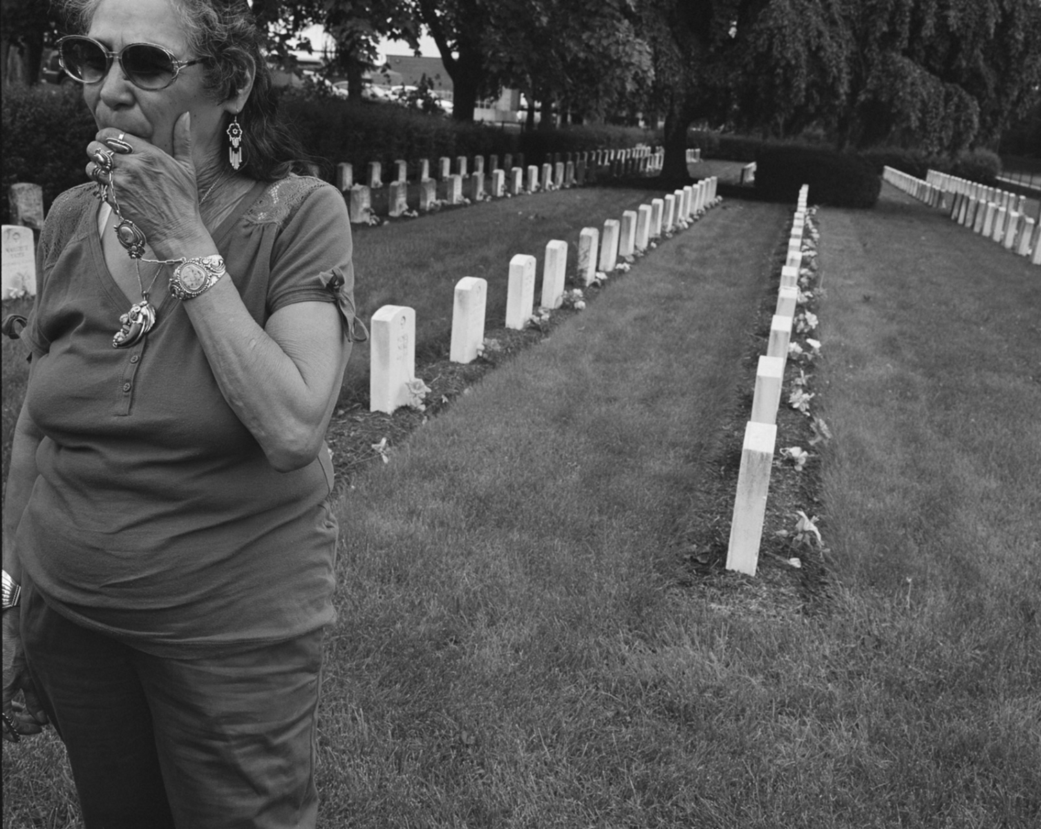 An indian women marks memorial day by placing flowers on the graves of
